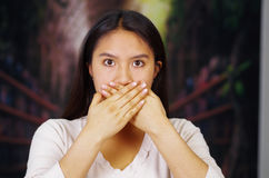 Young brunette woman wearing white sweater covering mouth using hands, facing camera, hostage concept Stock Photos