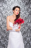 A young brunette woman in a white bridal dress. A young and beautiful brunette Caucasian woman posing in a white bridal dress and holding a red bouquet of Stock Photos