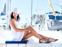 Young brunette woman in a white dress on a boat stock images