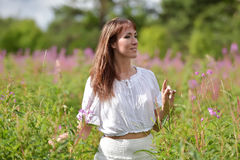 Young brunette woman in white dress Stock Images