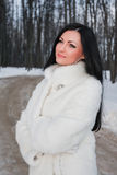 Young brunette woman in white fur coat Stock Image