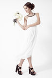 Young brunette woman and white roses. White Background. Royalty Free Stock Photos