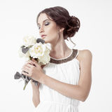 Young brunette woman and white roses. White Background. Royalty Free Stock Photography