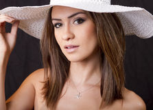 Young  brunette woman with white straw hat. Young  brunette woman wearing a white straw hat Stock Photography