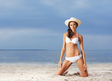 A young brunette woman in a white swimsuit on the beach Stock Images