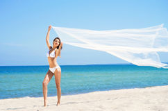 A young brunette woman in a white swimsuit on the beach Stock Photo
