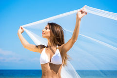 A young brunette woman in a white swimsuit on the beach Royalty Free Stock Photos