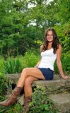 Young brunette woman in white tank top. Beautiful young brunette woman standing in a white tank top and denim mini skirt (with cowboy boots) sitting on a Stock Photos
