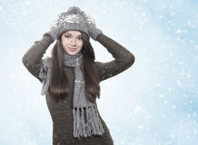 Young brunette woman in winter scenery. Young brunette woman with ahiny hair in hat, gloves and scarf on winter background stock photos