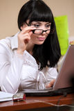 Young brunette working with laptop Royalty Free Stock Image