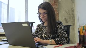 Young brunette is working, sitting at desk with laptop in modern office.