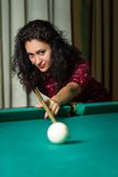 Young brunnete woman aiming to ball playing billiard. Stock Photography