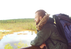 Young, brutal bearded guy standing on tower and enjoying views. Royalty Free Stock Photography
