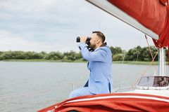 Young and brutal businessman with the beard in a stylish blue suit sits on the yacht ship and watching through the stock images