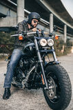 Young brutal man in a black jacket and glasses on motorcycle Royalty Free Stock Photography