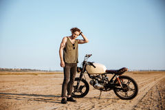 Young brutal man in black standing near a motorcycle. At the desert Stock Images