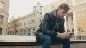 Young brutal man communicates in the messenger in a beautiful European city. Young brutal man uses a smartphone while sitting in a beautiful European city. Slo stock video