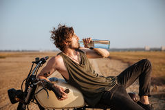 Young brutal man laying on his motorcycle and drinking water Stock Photos