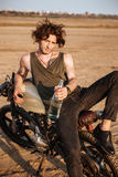 Young brutal man laying on his motorcycle and holding bottle Royalty Free Stock Image