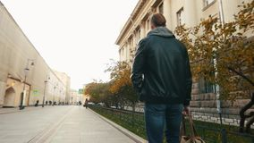 Young brutal man walks through an empty European city at dawn. Young brutal man walks through a beautiful European city at dawn. Slo-mo stock video