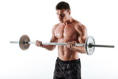 Young brutal muscular man exercising with barbell, looking aside Royalty Free Stock Photos