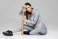 Young brutal sportive girl in sportswear looking at camera sitting with bit over white background. Copy space Royalty Free Stock Photos