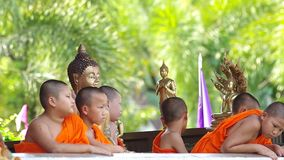 Young buddha novices in temple. Chiang Mai, Thailand - APRIL 13, 2015: Young buddha novices stayed around Buddha statue on Songkran day April 13, 2015 in Chiang stock footage