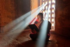 Young Buddhist monk. Bagan, Myanmar - Desember 7: Young buddhist monk reading inside old pagoda temple in mandalay historical park. Desember 7, 2016, Myanmar stock photography
