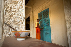 Young buddhist monk. CAN THO, VIETNAM - JAN 4, 2014 - Young buddhist monks walks out of monastery doorway Royalty Free Stock Image