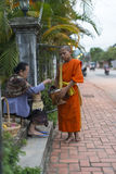 Young buddhist monk getting alms. Food is given to a young buddhist monk in Luang Prabang in Laos during an alms round early in the morning royalty free stock photos
