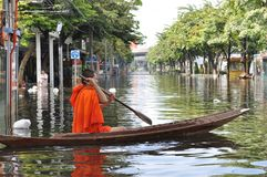 A young buddhist monk keeps smiling as he is rowing his boat in a flooded street of Bangkok, Thailand on the 11th of November 2011.  Royalty Free Stock Image
