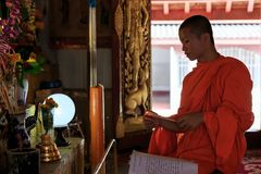 Young Buddhist Monk light incense sticks Stock Images