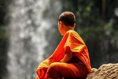 Young buddhist Monk is dreaming at the Waterfall. A young Buddhist monk sits aloof, watching the waterfall and dreaming to himself. Phnom kulen national park stock photos