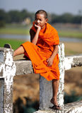 Young Buddhist monk sitting on a bridge Stock Photos