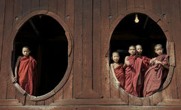 Young Buddhist Monks 2. Young Buddhist monks in the Shwe Yaungwe monastery near Inle Lake, central Myanmar. The monastery is special because of it's oval windows Stock Photo