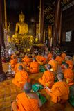Young buddhist monks praying in front of the Buddha image stock photo