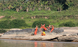 Young Buddhist Monks Sit Along the Mekong River, Laos. Young Buddhist monks sit along the stunning Mekong River catch some rays in front of a green, lush Royalty Free Stock Photo