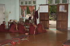 Young Buddhist monks sit while being taught. Stock Image