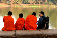 Young Buddhist monks talk with new  friend Stock Photos