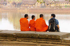 Young Buddhist monks talk with new  friend Stock Photo