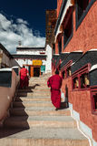Young Buddhist monks walking on stairs along prayer wheels in Thiksey gompa Stock Photo