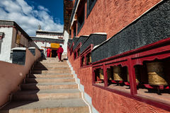 Young Buddhist monks walking on stairs along prayer wheels in Thiksey gompa Royalty Free Stock Images