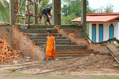 Young Buddhist novice holding a trowel at temple construction si Stock Images