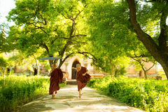 Young Buddhist novice monks running outside monastery. Two little playful Buddhist novice monks running outdoors under shade of green tree, outside monastery Royalty Free Stock Photography