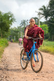 Young buddhist novice ride a bicycle near Hpa-an in Myanmar Royalty Free Stock Image
