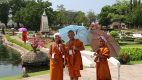 Young buddhists in yellow vestments at excursion in Mini Siam park in Pattaya, Thailand stock footage