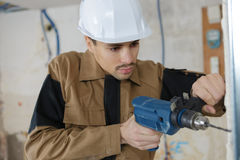 Young buider drilling wall with drill perforator. Young buider drilling the wall with drill perforator stock image