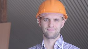 Young builder gesturing good quality at the building under construction. Young builder gesturing good quality at the building under construction stock video footage