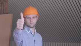 Young builder gesturing good quality at the building under construction. Close up of caucasian bearded man showing his. Thumb up. Construction worker in orange stock video footage