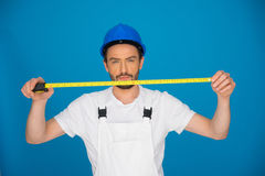 Young builder holding up a measuring tape Stock Photo